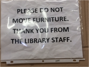 Image of a printed, wrinkled sign shoved in a plastic sleeve telling patrons not to do something.